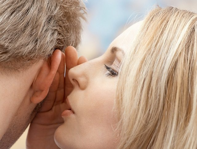Woman whispering in man's ear --- Image by © Royalty-Free/Corbis