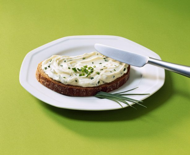 Slice of bread with cream cheese and chives on white plate