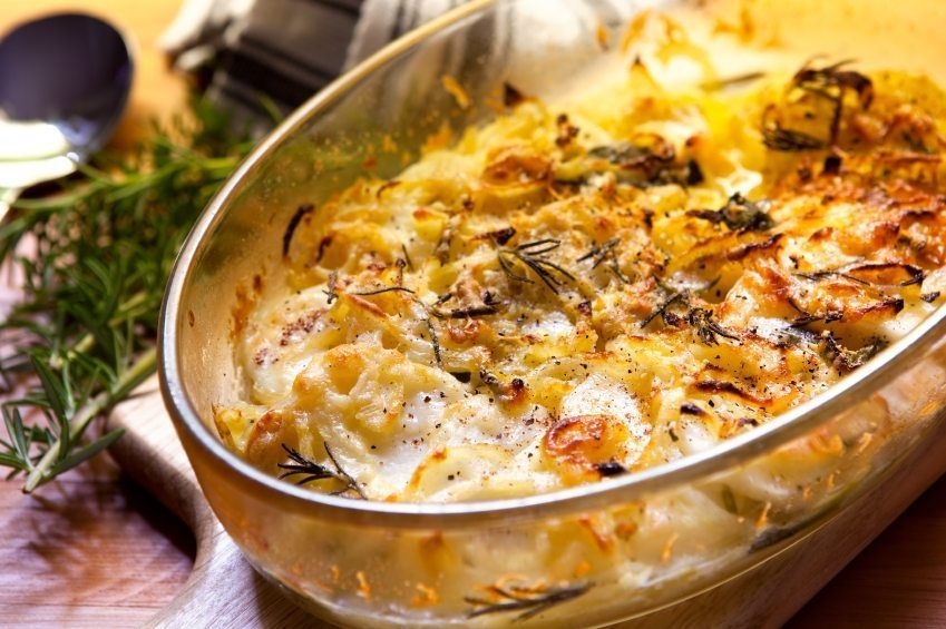 Potato and onion gratin with rosemary, in warm light.
