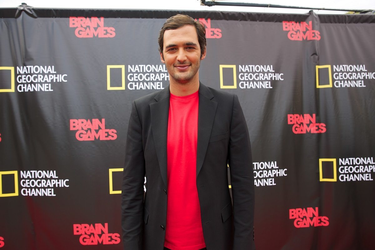 NEW ORLEANS, LA.- Jason Silva standing in front of a step & repeat covered in the National Geographic Channel and Brain Games logos.  (Photo Credit: NG Studios/Chris Van Cleef)