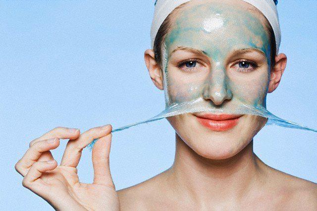 A woman peeling a face mask off her face --- Image by © Lena Clara/fstop/Corbis